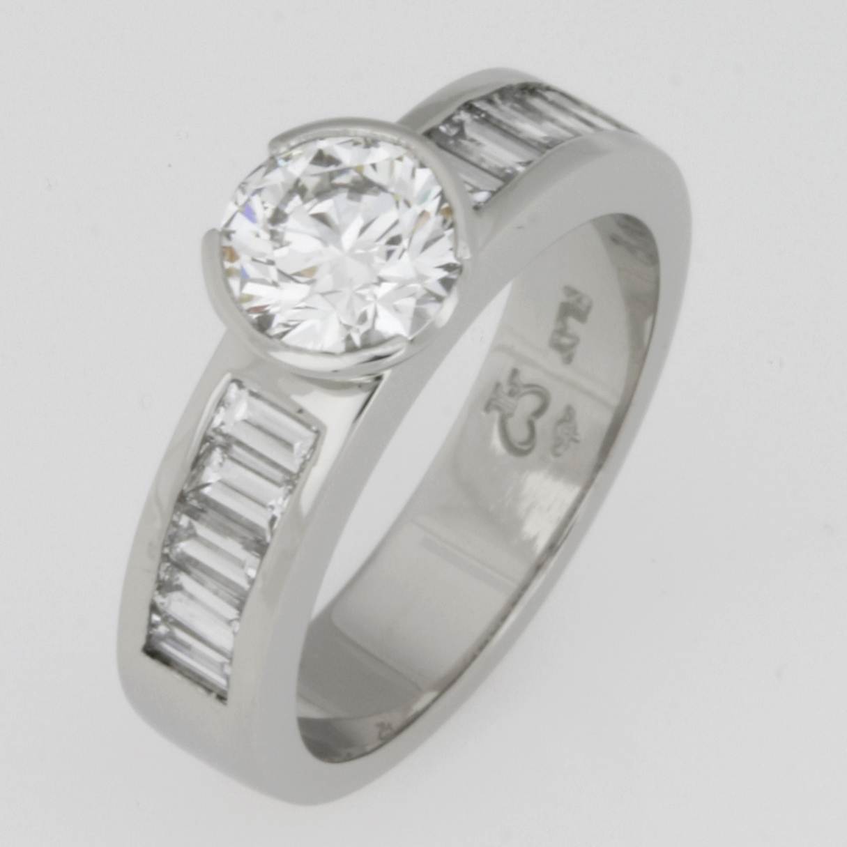 Handmade ladies platinum engagement ring featuring a brilliant cut diamond baguette diamonds