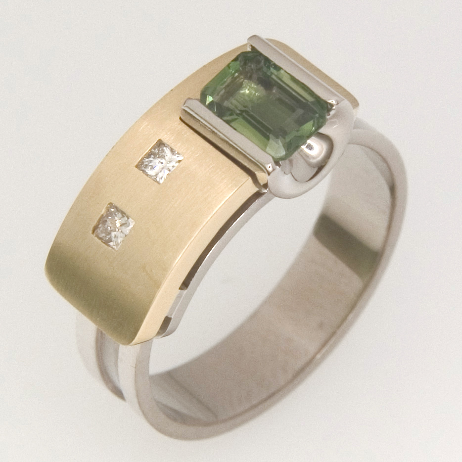 R067 Handmade ladies 18ct yellow and white gold Archie style ring featuring an emerald cut 6mm x 4mm green tourmaline and two 5pt princess cut diamonds. $2610