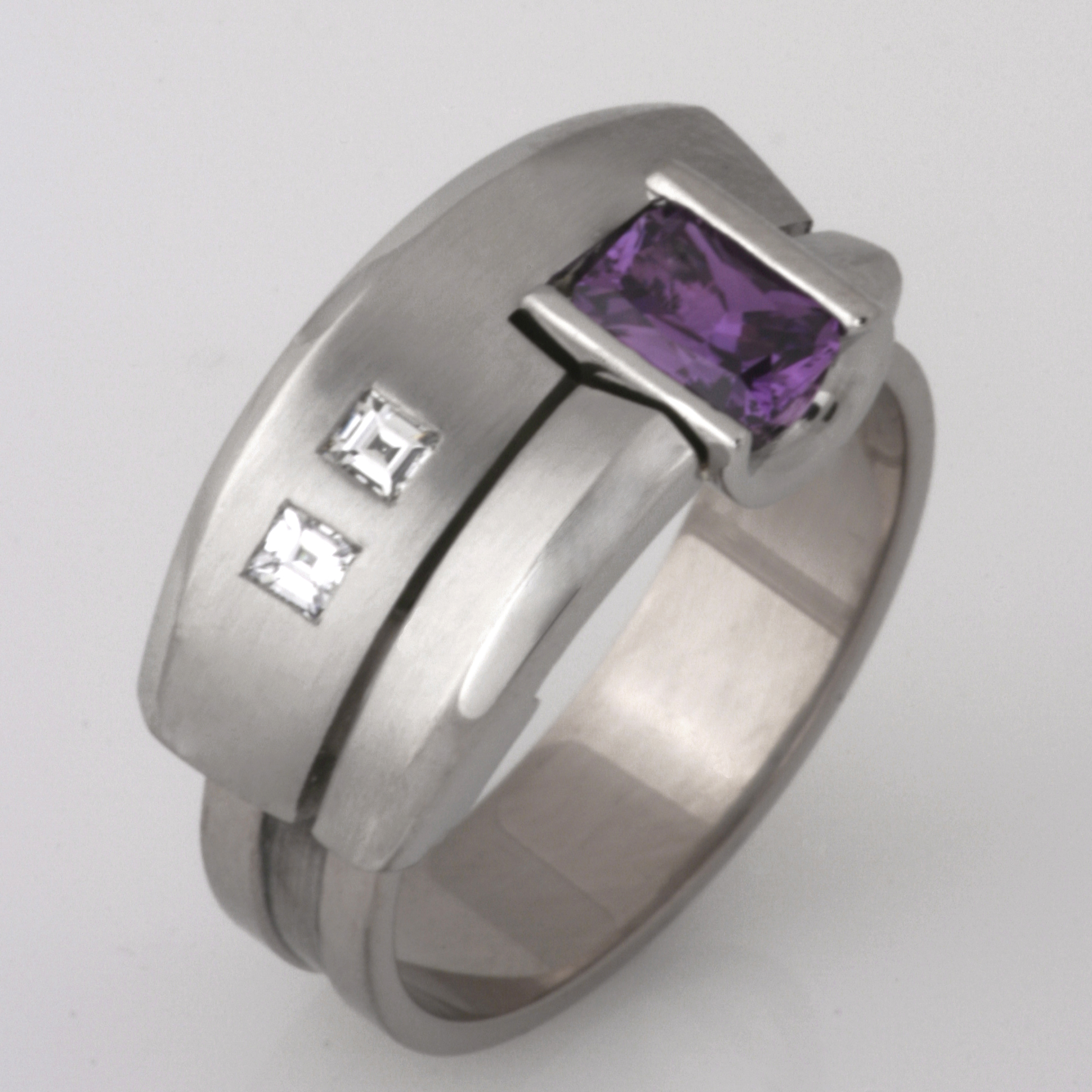 "R089  18ct white gold and palladium Archie style ring featuring a pink/purple Ceylon sapphire and two 2mm square Carre cut diamonds. Size ""O""  $3700"