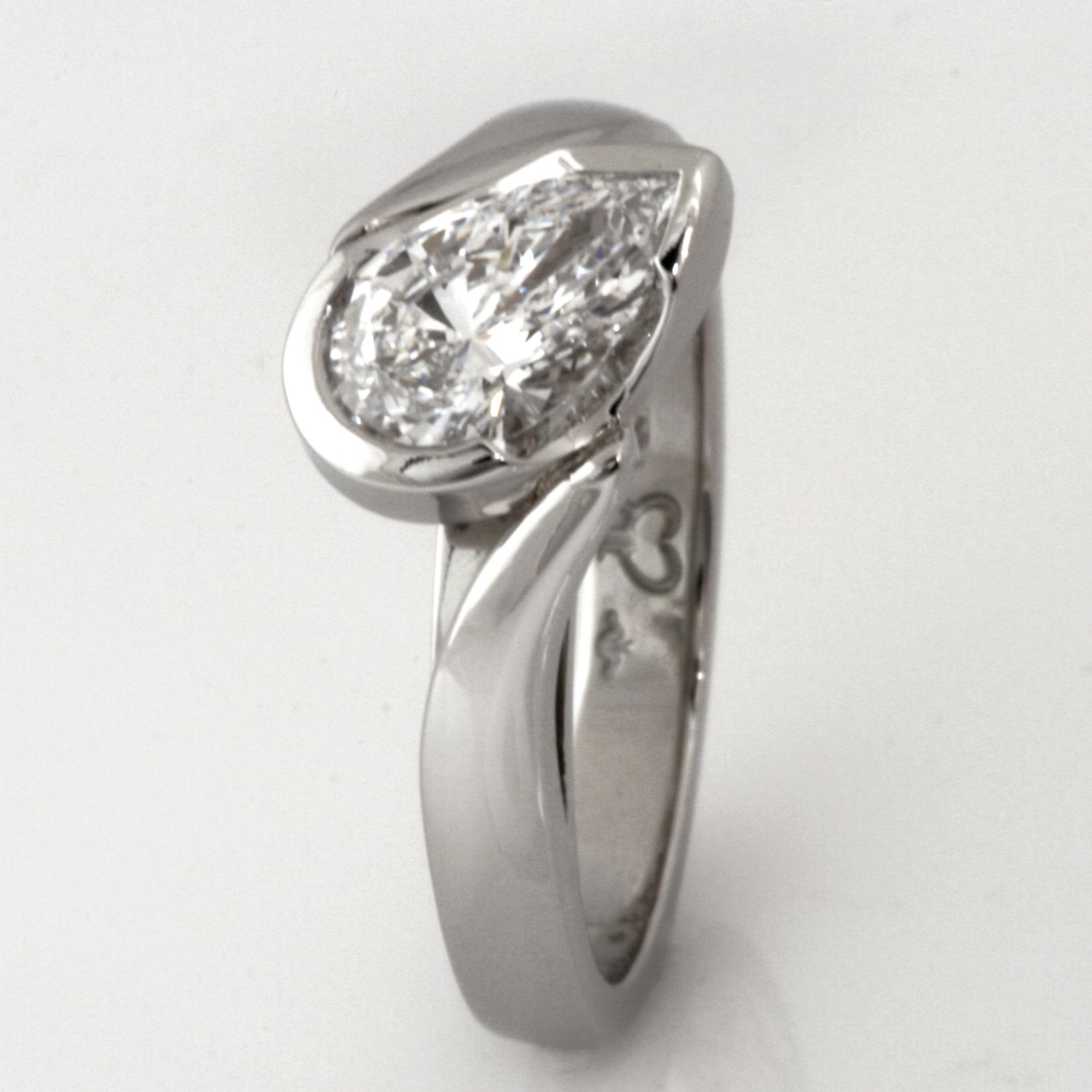 Handamde ladies platinum engagement ring featuring a pear shaped diamond