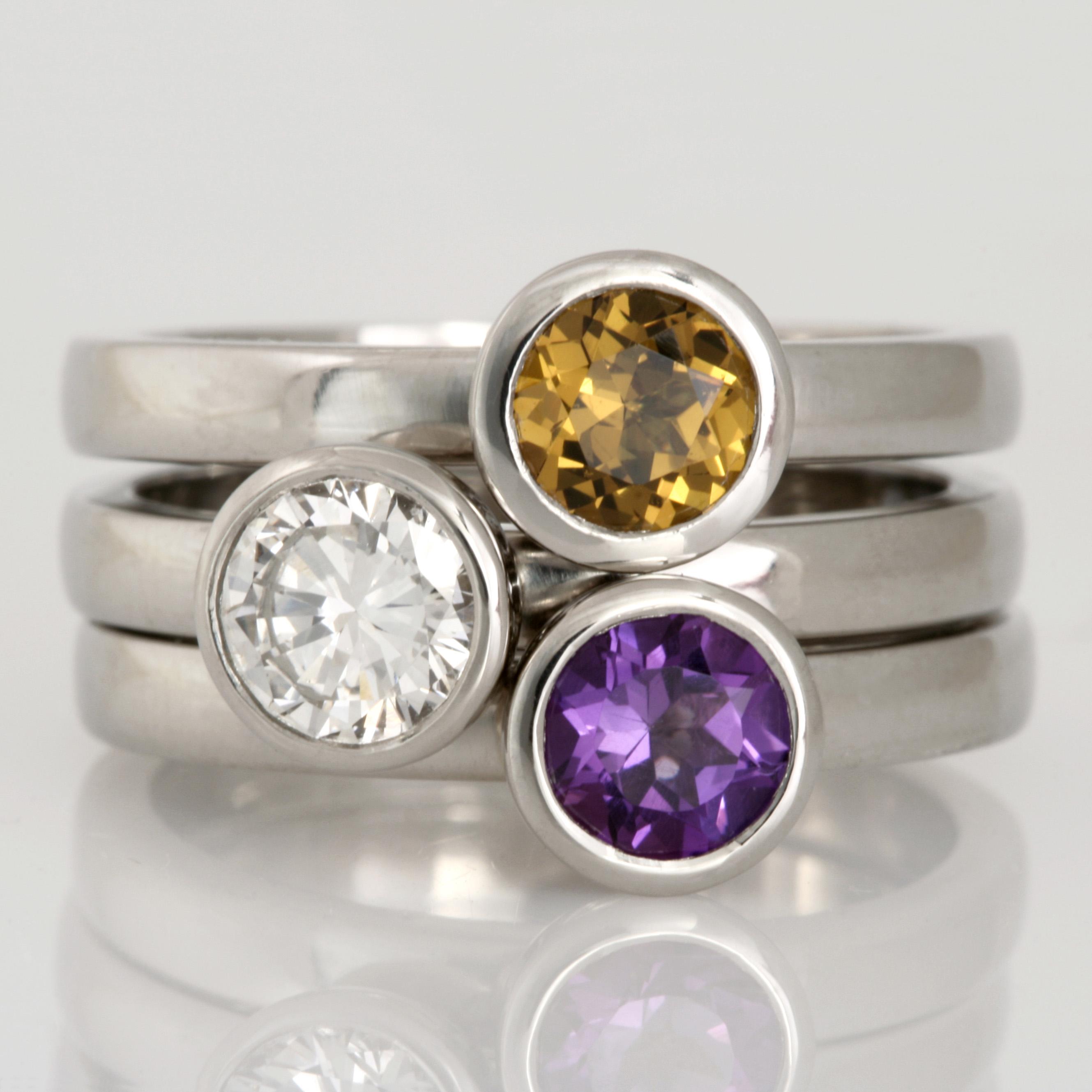 Three handmade ladies palladium stacker rings featuring an amethyst, diamond and Mali garnet