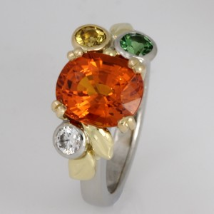 Handmade ladies palladium, 18ct yellow gold and 18ct green gold ring featuring a manderine garnet as the main stone and a tsavorite garnet and a mali grossular garnet and a diamond.