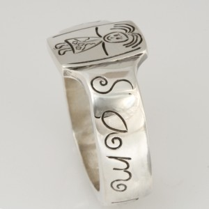 Handmade sterling silver ring featuring a hand engraved copy of a childs drawing on the ring