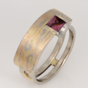 "R033 18ct yellow, white and marbled gold Archie style ring featuring a context cut rhodolite garnet. Size ""N""  $2380"
