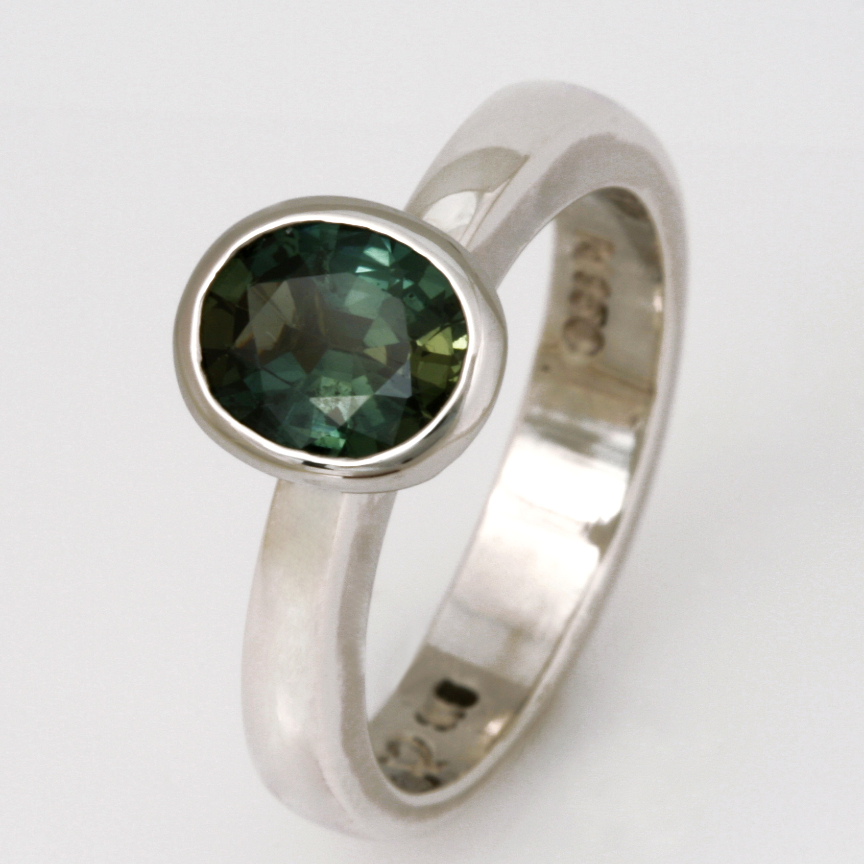Handmade ladies sterling silver with palladium and 9ct white gold ring featuring a green sapphire