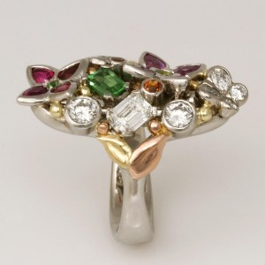 Handmade 'Dance of life'. Palladium, 18ct green gold and 18ct rose gold ring featuring diamonds, emeralds, tsavorite garnets, rubies, pink sapphires, greenish yellow chrysoberyl and spessartite garnets.