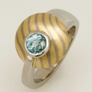 Handmade ladies palladium blue zircon ring featuring a 18ct yellow and white gold Mokume Gane disc