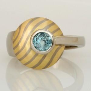 Handmade ladies palladium blue zircon ring featuring a 18ct yellow and white gold Mokume Gane disc
