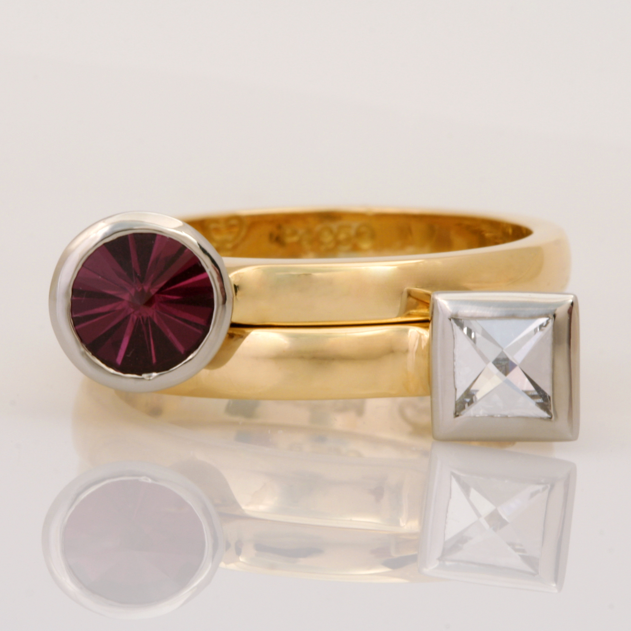 Handmade ladies 18ct yellow gold and palladium stacker rings featuring a Context cut diamond and a Spirit cut rhodolite garnet