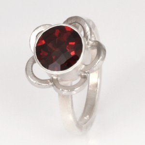 R148 Sterling silver ring with a palladium flower cut out surrounding an 8mm round checkerboard garnet.  $450