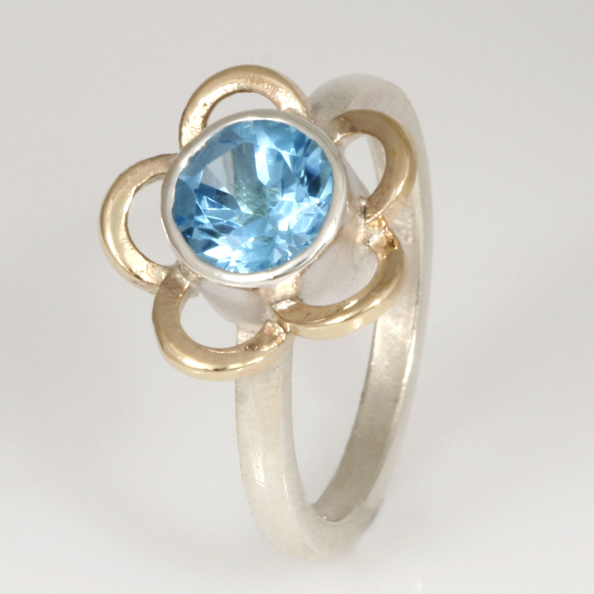 R146 Sterling silver ring with a 9ct yellow gold flower cut out surrounding a 7mm round blue topaz.  $390