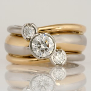 Handmade ladies 18ct yellow gold and palladium ring with platinum settings featuring three round brilliant cut diamonds.