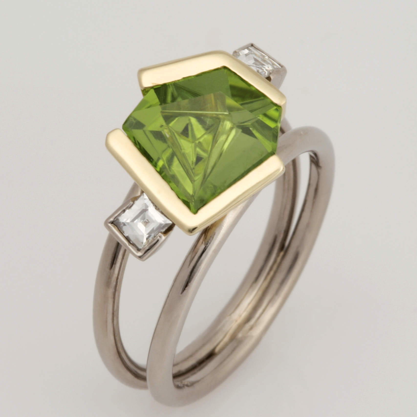 Handmade ladies 18ct white gold and 18ct green gold ring featuring a fancy cut peridot and tycoon cut diamonds.