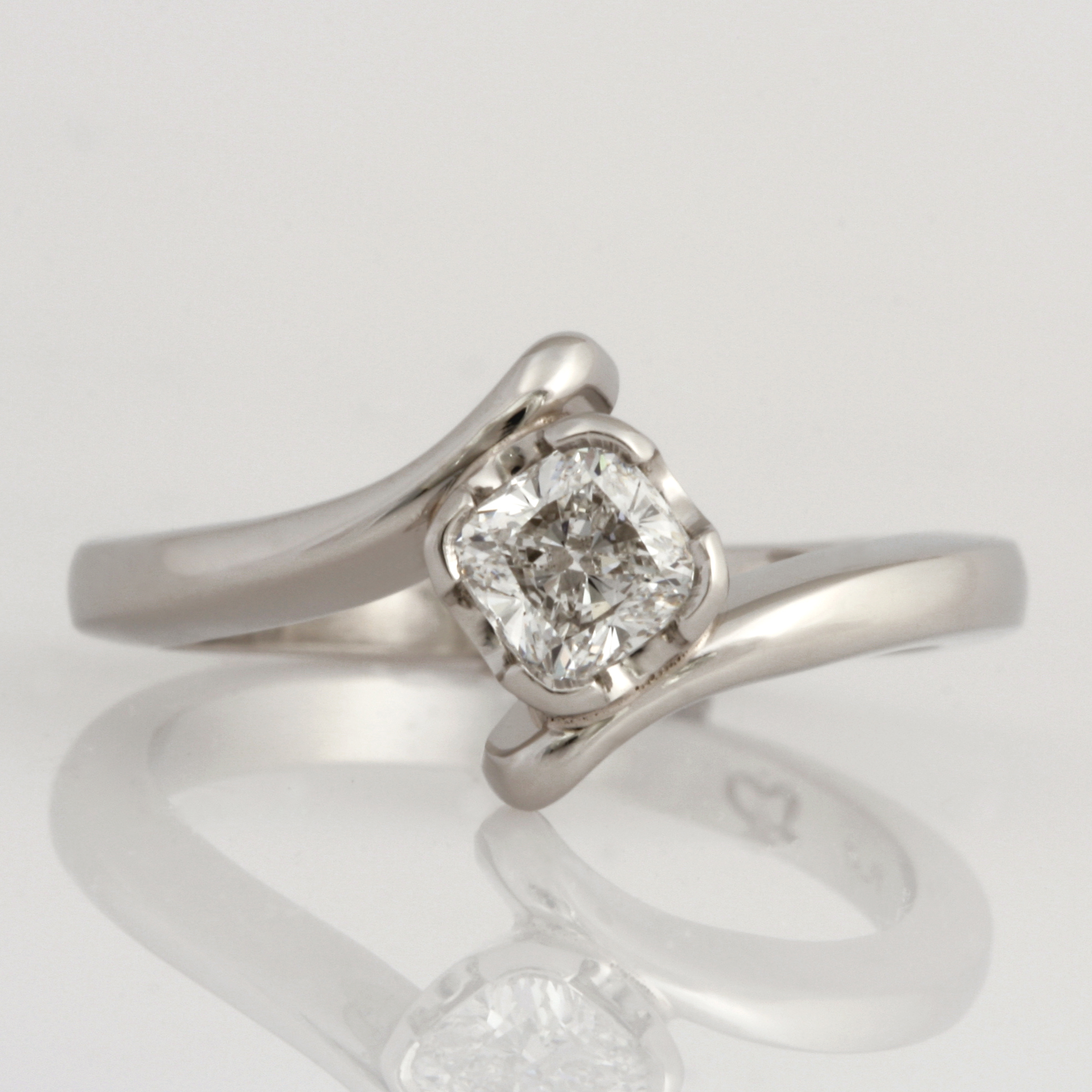 Handmade ladies platinum ring featuring a cushion cut diamond