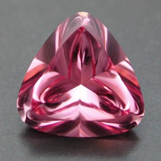 "Pink Sapphire This manmade pink sapphire is from a faceter in Berlin who has connections to the former labs of the ""Centralinstitute for Optics & Spectrography of the Academy of Science of the (former) German Democratic Republik"" that hold great stocks of experimental produced boules (crystals). This is a Ti-dotted corundum with a salmon pink colour. The Liquid Flower pattern works impressively in this lighter pink Sapphire. 6.61cts., 11.5 x 7.0 mm   $500"