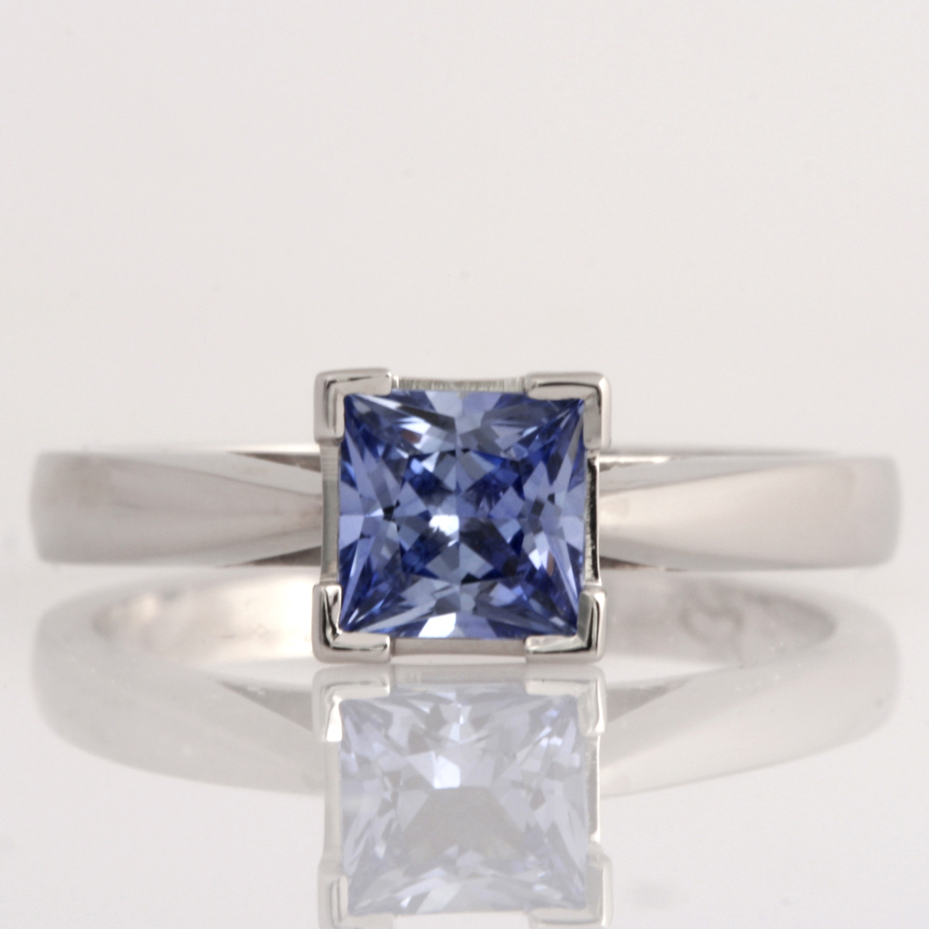 Handmade ladies platinum engagement ring featuring a square princess cut Ceylon sapphire