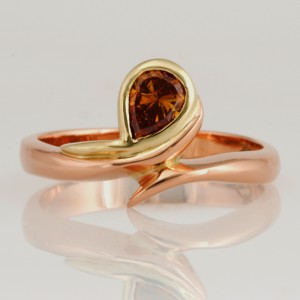Handmade ladies 18ct rose and green gold ring featuring a deep yellowish orange pear shape diamond