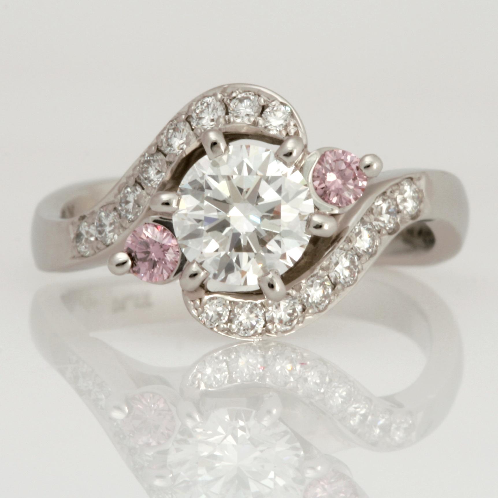 Handmade ladies platinum diamond engagement ring featuring pink and white diamonds.