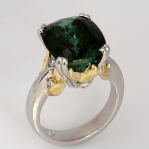 Handmade ladies platinum ring featuring 18ct green gold leaves, diamonds and a cushion cut green tourmaline.