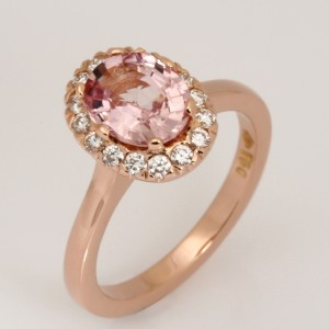 Handmade ladies 18ct rose gold engagement ring featuring an oval peach sapphire surrounded by a halo of white round diamonds