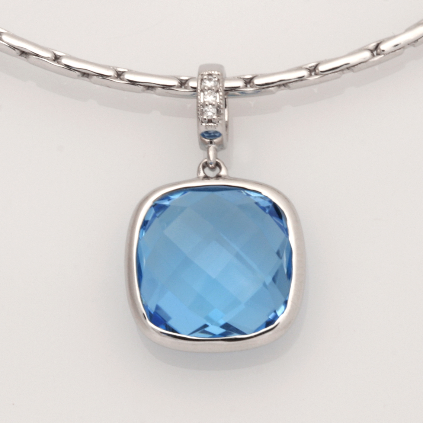 P110 – 9ct WG checkerboard 12mm cushion blue topaz pendant with diamond set bail 3=0.01cts $690