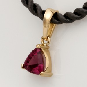 Handmade 18ct yellow gold pendant featuring a trilliant cut rhodolite garnet on a dark grey silk cord